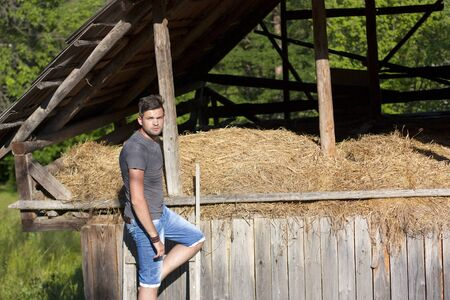 Handsome young man against stable of hay photo