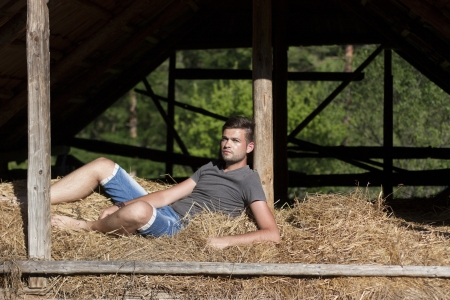 Handsome young man in the hay barn photo