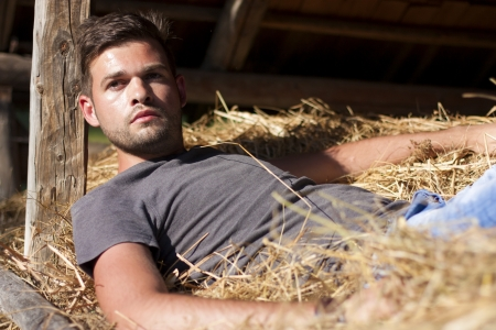 Handsome caucasian young man in the hay barn photo