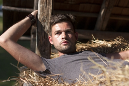 Handsome caucasian young man in the hay barn Stock Photo