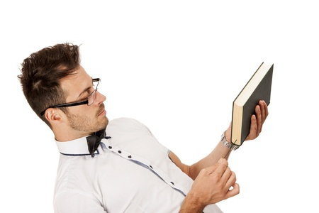 Young man holding a book and thinking isolated over white background