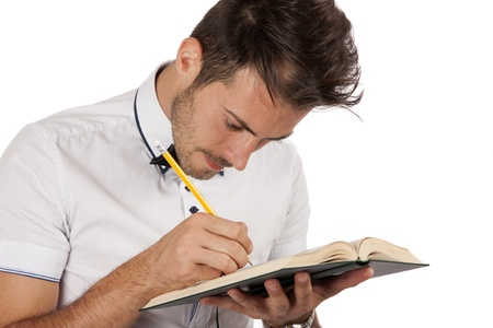 Young handsome man making annotations in a book, isolated over white background Stock Photo