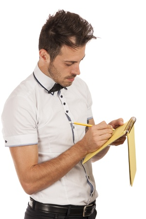Handsome young man  writing in notebook, isolated over white background