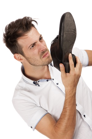 unpleasant smell: Young man holding one of his shoes close to his nose pulling a face, isolated over white Stock Photo