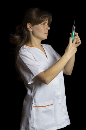 Young beatiful woman holding a syringe isolated over black