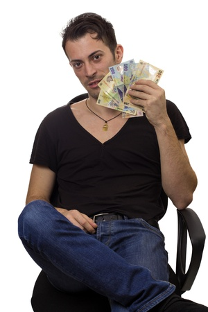 Young man sit on chair and hold money, isolated over white background photo