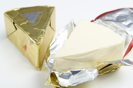 Triangle piece of cheese in golden foil  Standard-Bild