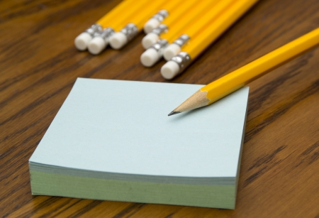 Block of post-it notes with yellow pencil on a wooden table  photo
