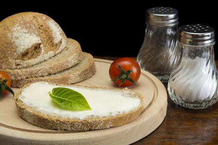 Close up image of spreading cream cheese on pumpernickel bread Stock Photo
