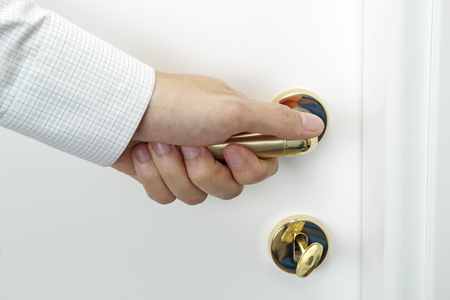 Business man hand opening a white wooden door photo