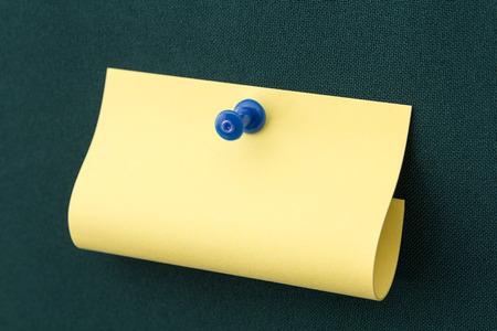 yellow pushpin: Yellow post-it note with blue pushpin on green board
