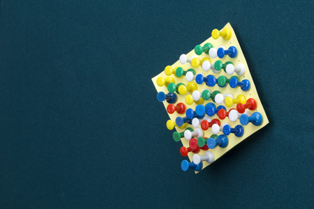 memorise: Yellow post-it note with many pushpins on a green board Stock Photo