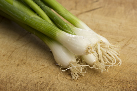green onions: Bundle of fresh green onions on a wooden chopping board Stock Photo
