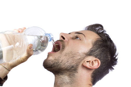 Portrait of young man drinking water from bottle isolated on white background photo