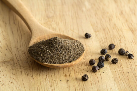 pepe nero: Mucchio di polvere di pepe nero su un cucchiaio di legno e pepe calli, profondità di campo