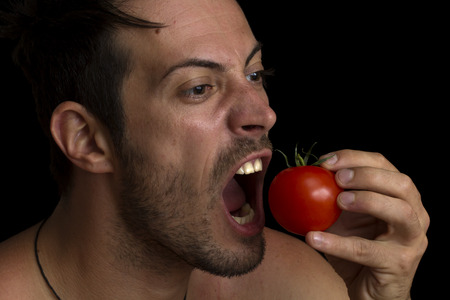 man biting a tomato isolated over black background photo