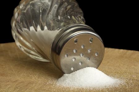 Spilt salt and salt shaker on wood with black background Stock Photo