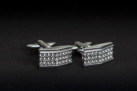 cufflink: Pair of silver cuff links over black background