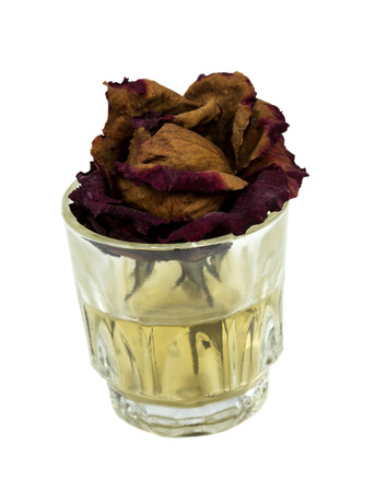 Withered rose in glass with dirty water on white background photo