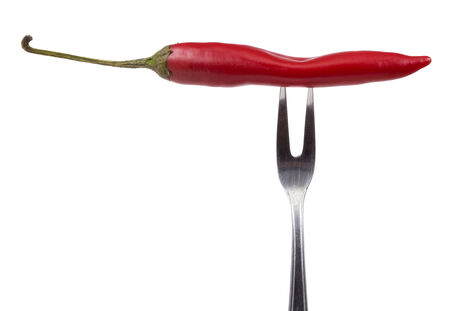 Red hot chili peppers on the fork isolated over white background photo