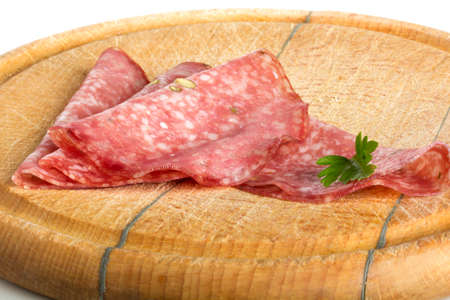 salami slices: Salami slices  and parsley on wooden board