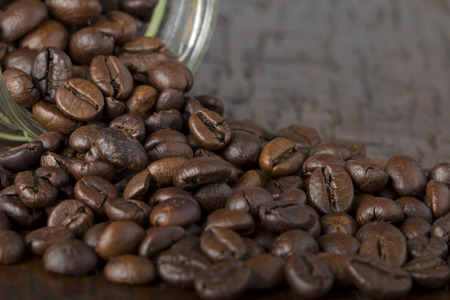 Glass jar with coffee beans on wooden table photo