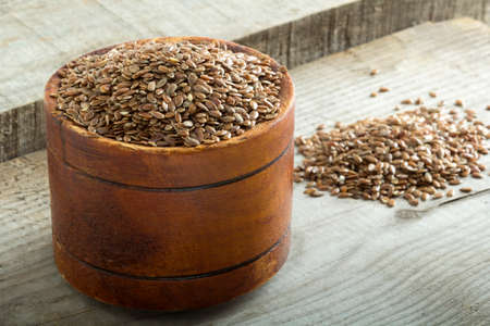 Flax seeds in bowl on wooden background photo