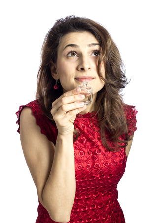 Young woman with a red dress smelling her perfume