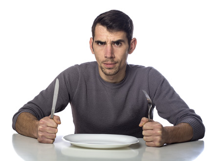Man at dinner table with fork and knife raised. Hunger strike isolated over white background 스톡 콘텐츠