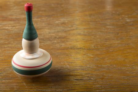 molinete: Spinning perinola sobre la mesa de madera vieja