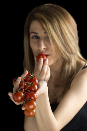 happy black woman: Portrait of a young beautiful blonde woman eating cherry tomatoes, isolated against black background, focus on cherry tomatoes Stock Photo
