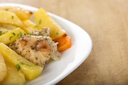 fine legs: Roasted chicken with potatoes and herbs on white plate Stock Photo