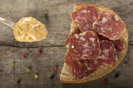 salami slices: Open sandwich of salami slices on whole grain bread and spoon with mustard