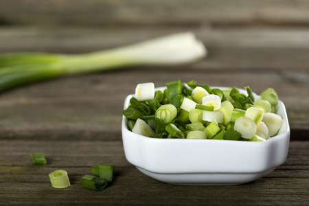 Fresh sliced scallions in white bowl on wooden background