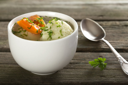 Traditional Chicken Soup with dumplings on a rustic wooden table with silver spoon