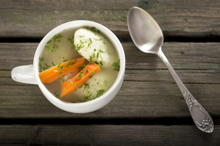 matzah ball: Traditional Chicken Soup with dumplings on a rustic wooden table with silver spoon