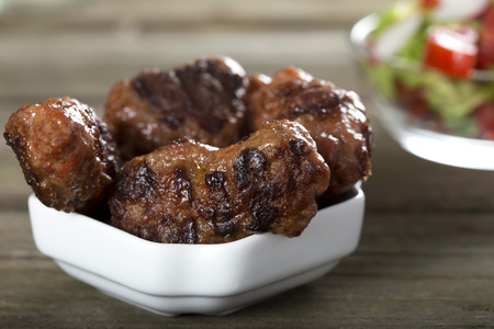 rustic food: Traditional food Meat Balls mici on a rustic wooden table with salad Stock Photo