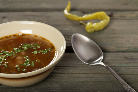 hot peppers: Bean soup in rustic bowl with silver spoon and one pickled hot peppers