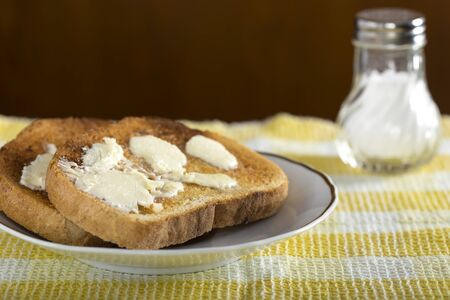 buttered: Two slices of white buttered toast on a plate with salt