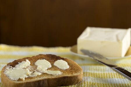 buttered: Slice of white buttered toast on a plate and knife