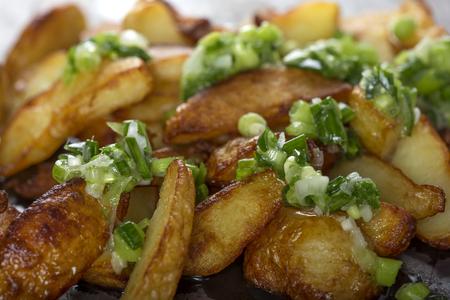 Fresh homemade crispy fried potato wedges with green garlic