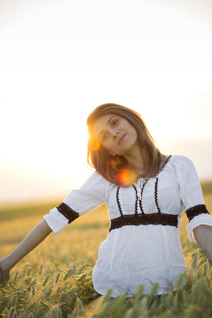 ie: Beautiful lady in wheat field at sunset wearing ie - romanian traditional costume Stock Photo