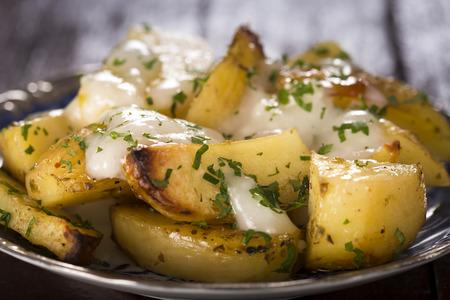 Knoblauch-Sauce (Aioli) über Bratkartoffeln mit Petersilie auf Teller Standard-Bild - 41499385