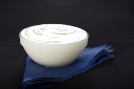 黒の背景に青のナプキンに新鮮なニンニクのディップ ソースのボウル 写真素材