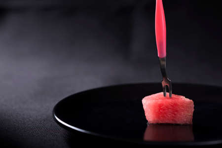 food       plate: One Slices of Watermelon on a Plate with a pink fork over black background