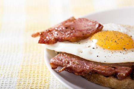 huevo: Tostadas con huevos fritos y bacon en un plato blanco