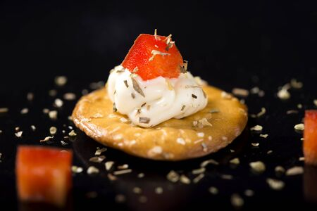 red bell pepper: One Cracker with Cream Cheese and red bell pepper over black background Stock Photo
