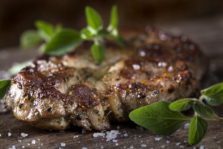 green herbs: Piece of of grilled neck pork with herbs on an old wooden table Stock Photo