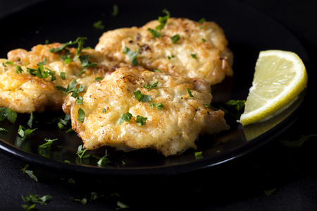 Fried chicken schnitzel with lemon on dark plate Stock Photo