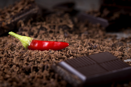 confiserie: Grated Chocolate with Red Chilli Pepper on wooden background closeup
